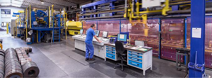 Produktionshalle mit einem Mitarbeiter am Bildschirm